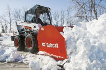 Snow pusher attachment to a Bobcat skid-steer loader removes snow from a parking lot.