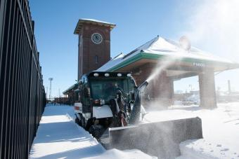 Bobcat snowblower attachment on 5600 Toolcat utility work machine clears snow in a municipal space.