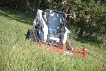 Bobcat flail cutter attachment is paired with a compact track loader to mow down a large area of overgrown grass.