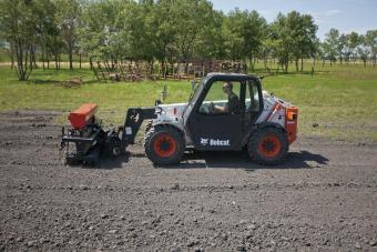 Seeder attachment mounted on a Bobcat V417 VersaHANDLER TTC plants grass in black dirt.