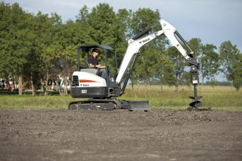 Auger attachment on an Bobcat E32 mini excavator digs into black soil.