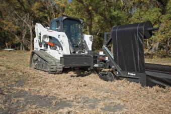 Bobcat compact track loader pulls the silt fence tight using the silt fence installer attachment.