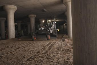 Sonic/slope system on a Bobcat compact track loader grading in an underground parking lot.