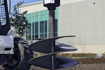 Bobcat auger attachment digs into black soil.