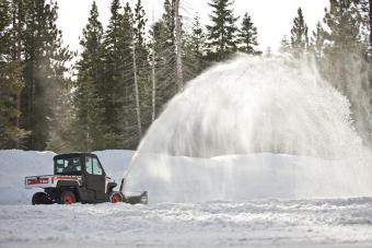 Bobcat 3650 UTV with snowblower attachment clears snow from a parking lot.