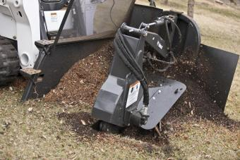 Tree stump is cleared with the Bobcat stump grinder attachment.
