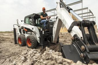 Bobcat S530 skid-steer loader with backhoe attachment digging a trench.