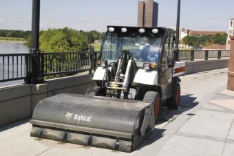 Toolcat 5600 utility work machine cleans a bridge with a sweeper attachment.