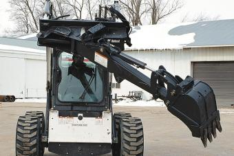 Bob-Tach Backhoe attachment allows a Bobcat skid-steer operator to dump spoil without skidding the loader.