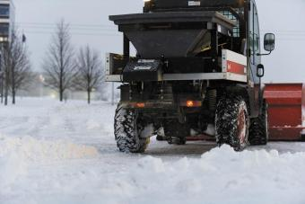 Spreader attachment being used to drop ice melt after a fresh snow.