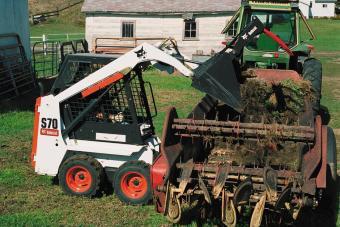 Bobcat S70 skid-steer loader loads manure into a trailer.