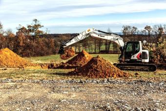 Operator Breaking Ground On Construction Jobsite With A Bobcat E145 Large Excavator With Bucket Attachment