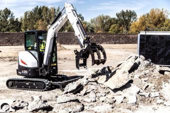 Bobcat E35 compact (mini) excavator and grapple attachment sorting concrete debris on a jobsite.