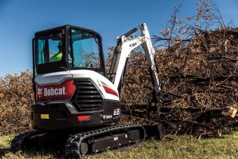 Bobcat E35 compact (mini) excavator moves a large tree branch onto a pile.