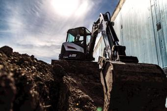 Bobcat E35 compact (mini) excavator reaching into a trench with a bucket attachment.