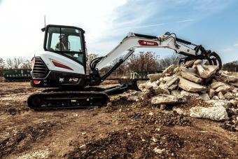 Bobcat Customer Using E42 Mini Excavator With Tine Grapple Excavator Attachment To Move Material On Construction Site