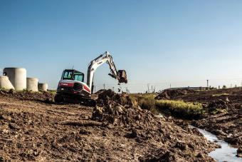 Bobcat R-Series E85 excavator moving dirt near a ditch.
