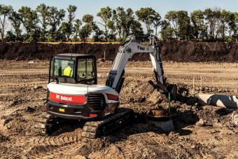 Bobcat R-Series E85 excavator digging trench for a pipeline.