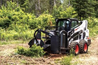 Bobcat MT55 mini track loader uses the stump grinder attachment to remove a stump from a field.