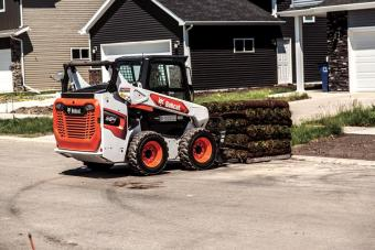 Landscaper Using Bobcat S64 Skid-Steer Loader With Pallet Fork Attachment To Move Sod On Residential Jobsite