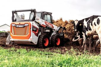 Bobcat S76 Skid-Steer Loader Hauling Cattle Feed With Grapple Loader Attachment