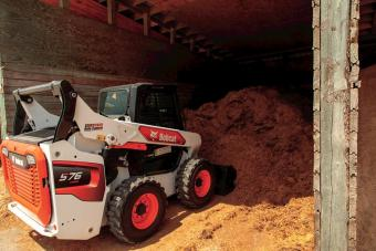 R-Series Skid-Steer Loader From Bobcat Company With Bucket Loader Attachment Moving Material On Farm Operation