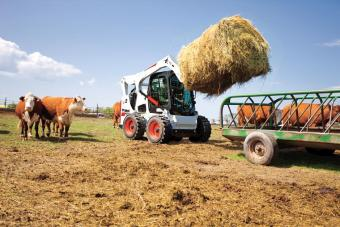 Bobcat S770 Skid-Steer Loader hauling hay in a pasture.