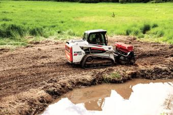 Bobcat T550 Compact Track Loader with seeder attachment.