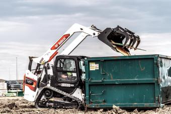 Construction Worker Using Bobcat T64 Track Loader With Industrial Grapple Attachment To Drop Plywood Into Jobsite Dumpster