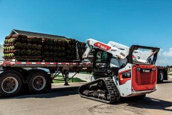 Skid-Steer Loader With Tracks Moving Sod With Pallet Fork Loader Attachment