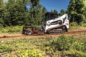 Bobcat skid-steer loader with a soil conditioner attachment prepares soil for planting.