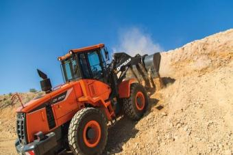 Doosan DL200-5 wheel loader carries a bucketful of material up an access road.