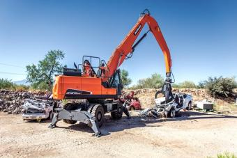 Doosan DX210WMH-5 material handler separates metal scrap with grapple attachment