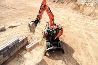 Doosan DX140W-5 wheeled excavator lifts wall block with bucket.