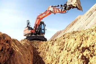 Doosan DX140W-5 wheeled excavator digs with bucket.