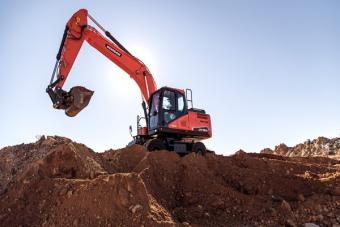 Doosan DX190W-5 wheel excavator digging with bucket attachment.