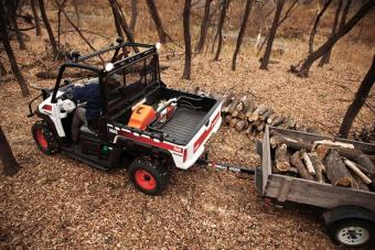 Bobcat 3600 utility vehicle with chainsaw in cargo box.