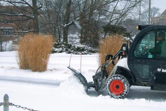 Snow blade (snowblade) attachment is used on a Toolcat utility work machine to clear snow from a university campus sidewalk.