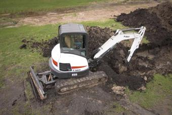 Bobcat E55 compact excavator (mini excavator) with extendable arm digs in a city park.