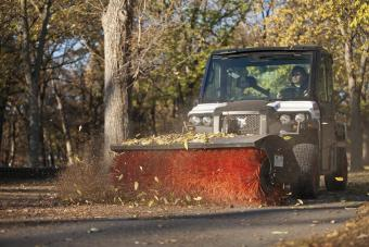 Bobcat 3650 UTV with an angle broom attachment sweeps leaves off a paved path.