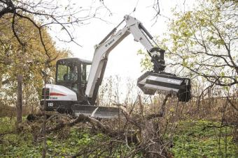 Bobcat E45 compact excavator with flail mower attachment clears downed branches in a wooded area.