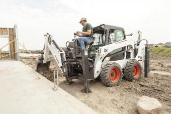 Bobcat S530 skid-steer loader digging next to a foundation with a backhoe attachment.