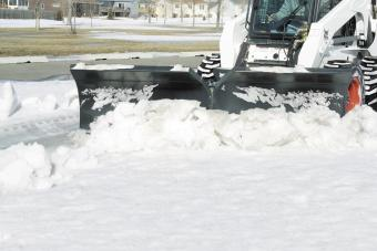 Bobcat snow V-blade attachment clears snow from a sidewalk in a wooded area.