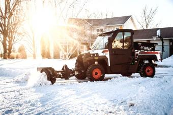 Bobcat 3650 utv with a snow v-blade attachment clears a residential driveway.