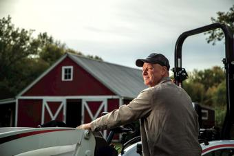 Farmer Standing In Front of Bobcat CT2025 Compact Tractor With Red Barn In Background