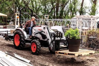 Landscaper Hauls Shrubs Using Pallet Fork Attachment On CT2040 Compact Tractor