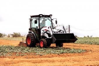 Farmer Tilling Field In Preparation For Planting Using Bobcat CT2540 Compact Tractor With Three-Point Tiller Implement