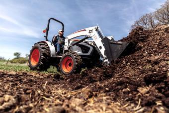 Bobcat CT4050 With Front-End Loader Digging Into Dirt Pile On Rural Property