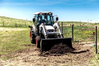 Acreage Owner Digging Dirt Using Bobcat CT5555 Compact Tractor With Front-End Loader