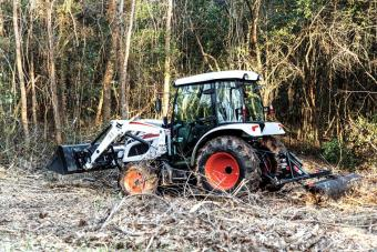 Bobcat CT5558 Compact Tractor With Enclosed Cab Using Tine Rake To Clear Overgrown Area of Acreage